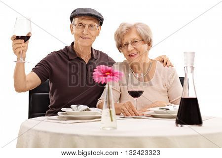 Senior man and woman posing seated at a dinner table with red wine isolated on white background