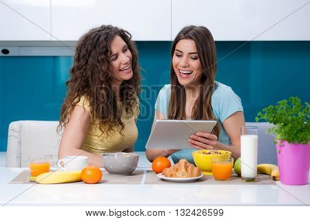 Two woman friends taking breakfast in the kitchen and having fun, talking and laughing.  catching up on social media on tablet deice as sitting at the dining table at home.