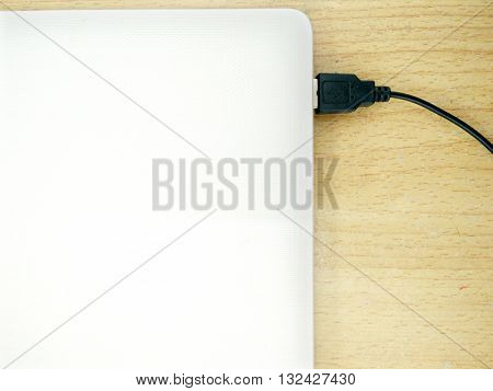 Laptop on wooden desk with note book.