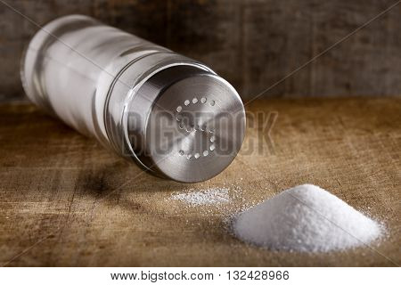 Lying down glass salt cellar and spilled salt on a wood background
