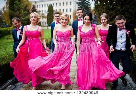 Four Groomsmen And Four Bridesmaids Having Fun, Stylish Friends At Wedding