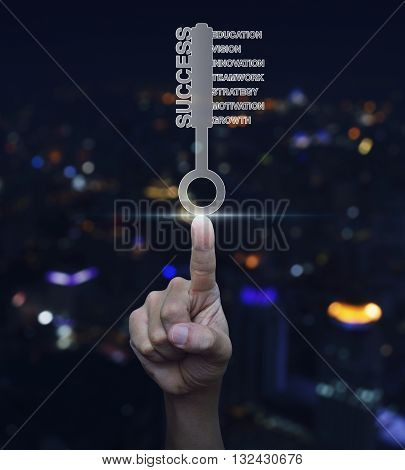 Hand pressing key with business words over blurred light city tower background Success business concept