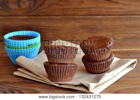 Perfectly chocolate cupcakes on paper and wooden table. Baking cakes at home. Soft sweet homemade muffins using silicone bakeware