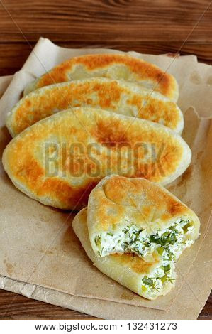 Fried pies with cottage cheese filling. Patties with cottage cheese, green onion and dill. Cheap recipe for homemade fried pies on a wooden background in rustic style. Easy meal idea. Close-up