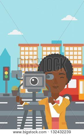An african-american camerawoman looking through movie camera on a city background vector flat design illustration. Vertical layout.