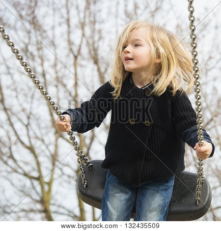 Little child blond girl having fun on a swing outdoor. Summer playground. Girl swinging high