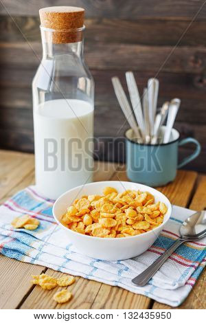 Tasty corn flakes in white bowl with bottle of milk. Rustic wooden background with plaid napkin. Healthy crispy breakfast snack.