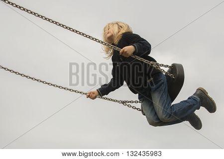 Little child blond girl having fun on a swing outdoor. Summer playground. Girl swinging high