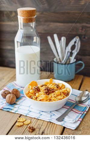 Tasty corn flakes with walnuts in bowl with bottle of milk. Rustic wooden background with plaid napkin. Healthy crispy breakfast snack.