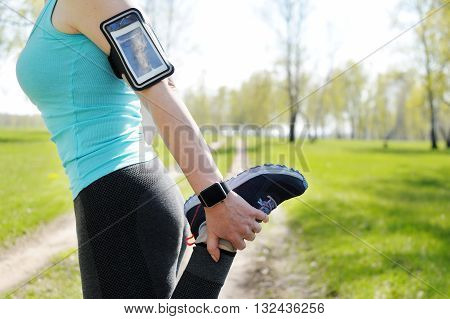 Running stretching - runner wearing smartwatch. Closeup of running shoes woman stretching leg as warm-up before run