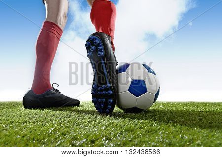 football player in red socks and black shoes running and dribbling with the ball playing outdoor on green grass pitch under a blue sky