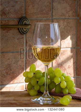 glass of wine and grapes in the wooden table