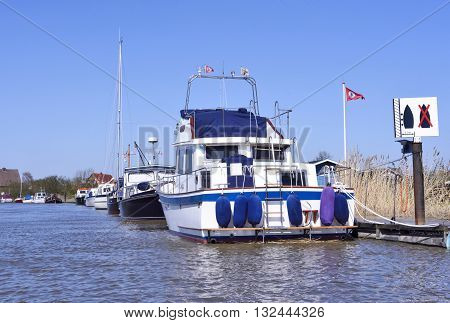 Anchored boats onto a river. Little pier or jetty with anchored sailing ships and motor boats. Sunny day.