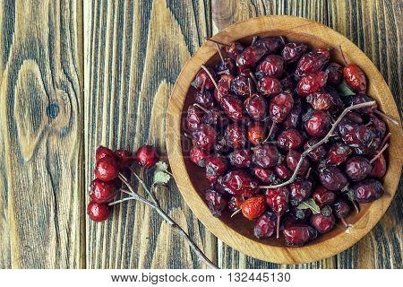 Rosehips in a wooden bowl on a wooden surface. Rosa canina hips.