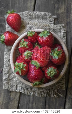 Wooden bowl filled with fresh ripe red strawberries from above