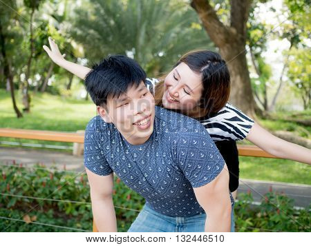 Young Asian Couple Having Piggy Back Together In Green Nature Background