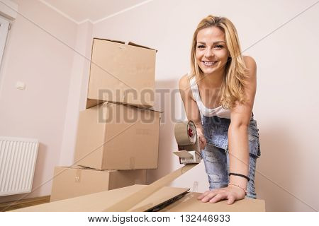 Young girl moving in a new apartmentstanding surrounded with cardboard boxes packing and taping boxes
