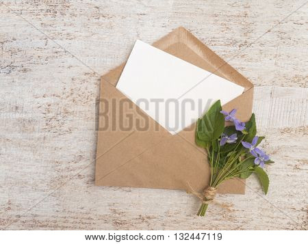 Brown paper envelope with white blank card and wild viola flowers bouquet tied with jute rope on the rustic white painted background