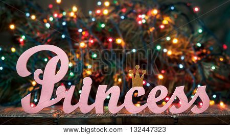 Christmas Decoration with the pink inscription Princess. Decorative letters forming word Princess with Christmas tree branch and lights on wooden background