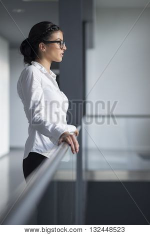 Strong confident business woman standing in an office building hallway