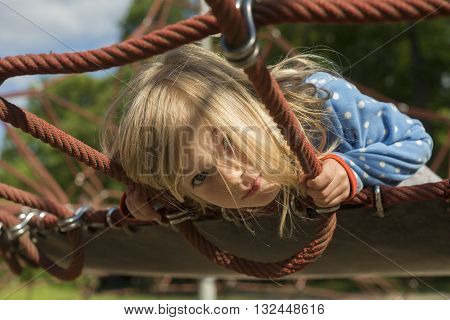 Pretty blond girl playing on rope of red web in summer