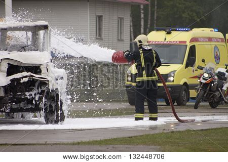 Firefighter extinguishes the fire with foam, rescue vehicles in the background