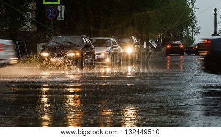 Heavy rain hitting a concrete sidewalk while cars drive by. Selective focus