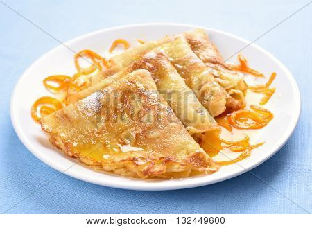 Crepes with orange syrup on white plate