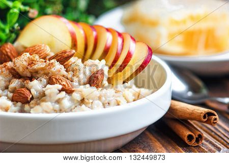 Organic oatmeal porridge in white ceramic bowl with apple, almond, honey and cinnamon. Healthy breakfast - health and diet concept on the wooden table, close up.