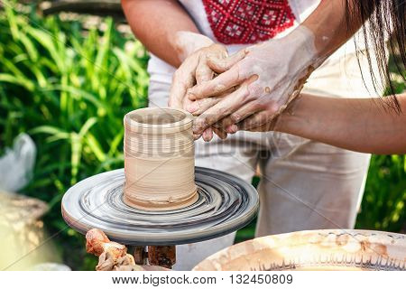 Hands working on pottery wheel. Sculptor, Potter. Human Hands creating a new ceramic pot. Female Potter creating a bowl on a Potters wheel the master potter helping her. Pottery Skill Workshop Concept