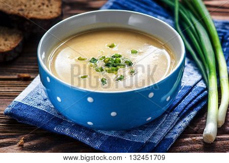Homemade vichyssoise cream soup served with chives, in blue bowl on wooden table.