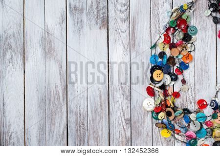 Handmade bright colored jewelry made of plastic buttons on the white wooden background. Place for text.