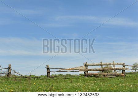 Old rickety wooden fence in ukrainian village with blue sky and green blooming field background