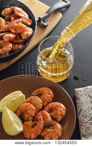 Fried shrimp on a platter, in the background filled with beer and a frying pan with shrimp.