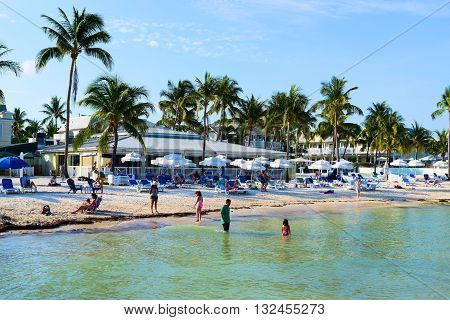 May 16, 2016 in Key West, FL:  Tourists sunbathing on the sandy beach and swimming in the warm ocean water taken at the Southernmost Point Beach Resort where tourists can visit in Key West, FL