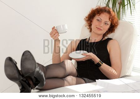 Young businesswoman rests at the table in the office.