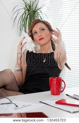 Young businesswoman rests at the table at the office.