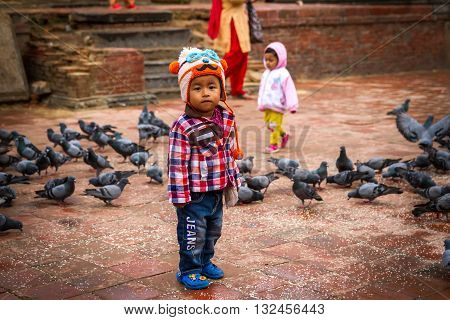PatanNepal - March 26 2016: Kids are playing with Pigeons and boy is feeling shy while taking photographs.