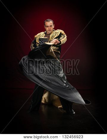 Male dancer dressed as a matador on a dark background.