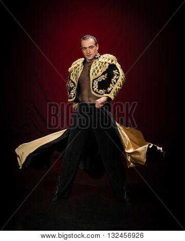 Male dancer dressed as a matador on a dark background.