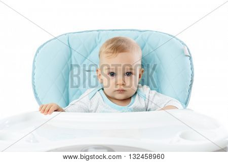 Sweet small girl sits in baby chair on a white background.