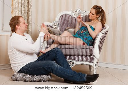 The husband does massage of feet of the pregnant wife of the house. Happy pregnant family.