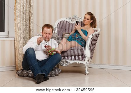 The husband does a pedicure to the pregnant wife of the house. Happy pregnant family.