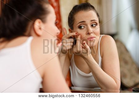 Unhappy young woman finding an acne on a cheek, sits before a mirror.