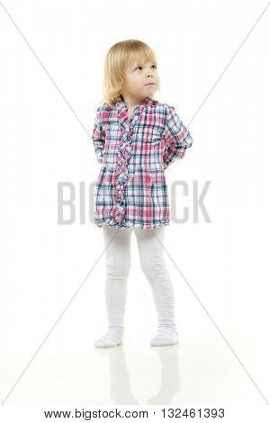 The little girl hides hands behind the back and looks upwards on a white background.