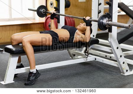 Sports young woman doing exercises with barbell on bench in the gym.  Bar Bench Press.