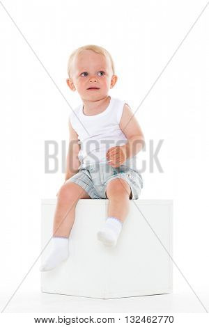 Unhappy yearling baby boy sits on cube on a white background.