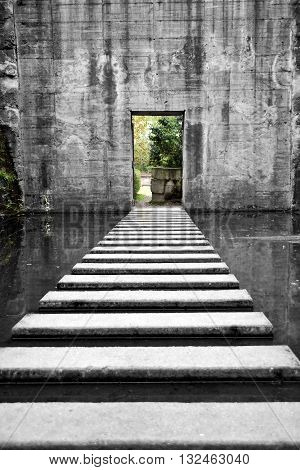 Old bomb shelter, with steps through water, sullen scene.
