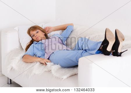Tired young well dressed businesswoman is sleeping lying on couch.