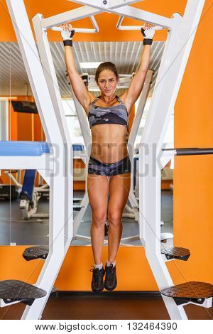 Sporty woman is doing exercises on power training apparatus in the gym. Pulling up on the horizontal bar.